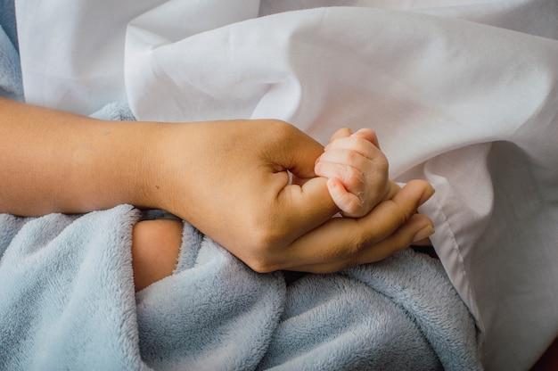 Крупным планом нежные руки новорожденного ребенка на ладони матери