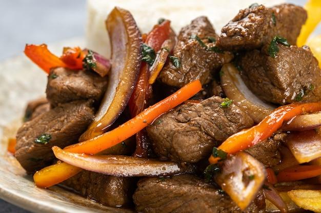 ライトの下で野菜とおいしいロースト肉のクローズアップ