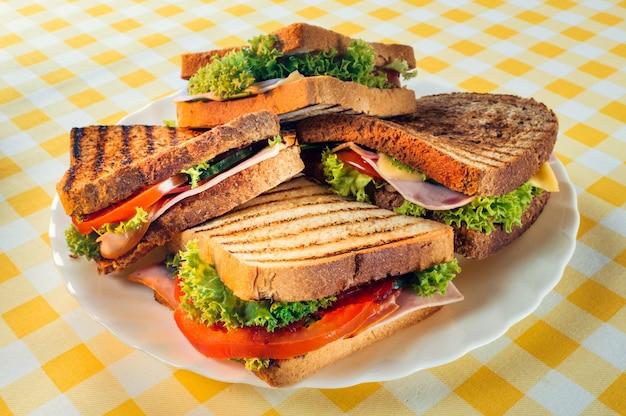 テーブルの上のプレートにハム、トマト、チーズ、ハーブとおいしいサンドイッチのクローズアップ
