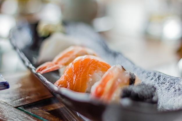 Крупным планом вкусные суши на традиционной черной тарелке