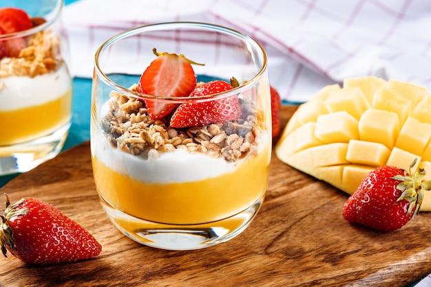 Крупным планом вкусный вегетарианский десерт с манго, мюсли, рикотта, украшенный клубникой на деревянной доске