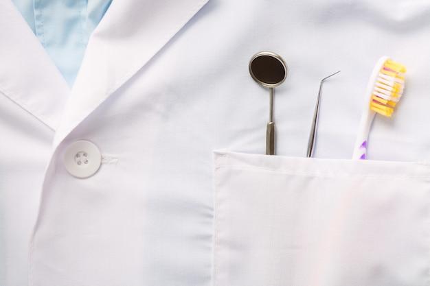 Крупный план зубоврачебного инструмента, зубной щетки и зеркала в белом кармане медицинской формы.