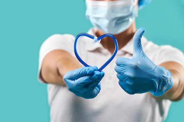ハートの形で唾液排出器を保持し、親指を上に表示している歯科医の手のクローズアップ。青い背景に分離