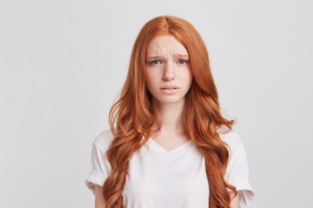 Крупным планом подавленная расстроенная рыжая молодая женщина с длинными волнистыми волосами