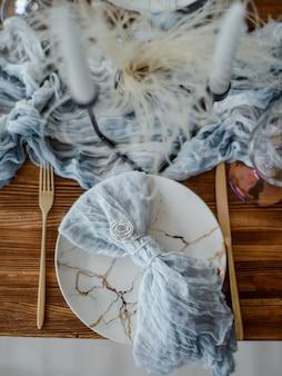 ほこりっぽい青い色で夕食の木製テーブルのクローズアップ。ヴィンテージゴールデンフォークとナイフ、ローソク足のキャンドル、ガーゼナプキンと白いプレート。結婚式のディナー。装飾。上面図