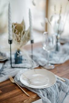 ほこりっぽい青い色で夕食の木製テーブルのクローズアップ。ヴィンテージゴールデンフォークとナイフ、ローソク足のキャンドル、ガーゼナプキンと白いプレート。結婚式のディナー。装飾。