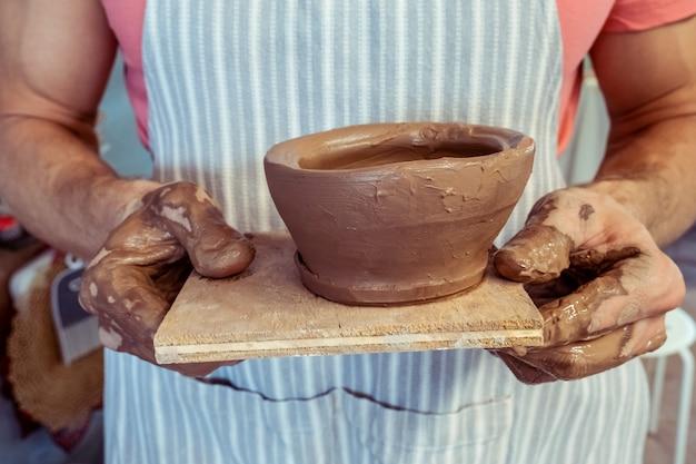 완성 된 갈색 점토 제품을 보여주는 더러운 남성 손의 근접 촬영