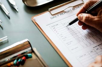 Closeup of doctor checking patient daily report checklist