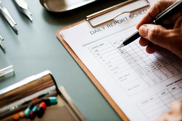 患者の日々のチェックリストをチェックしている医師の拡大写真