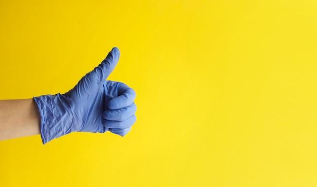 Крупный план руки доктора в голубой перчатке с большим пальцем руки вверх на желтой предпосылке.