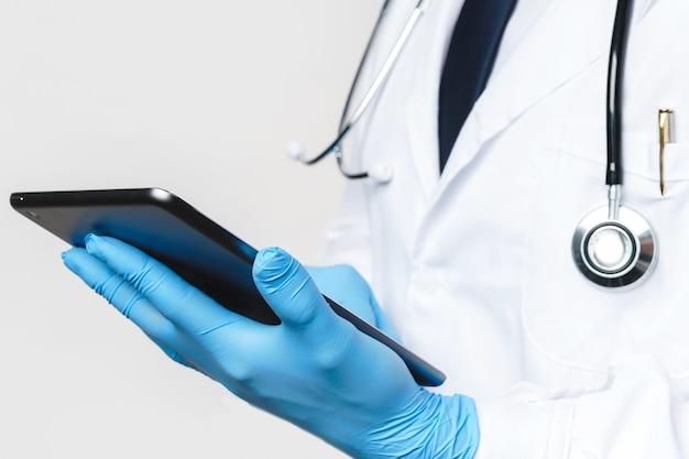 태블릿 pc와 라텍스 장갑에 의사의 손의 근접 촬영