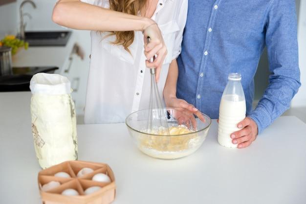 부엌에 유리 그릇에 젊은 부부가 손으로 때리는 팬케이크 반죽의 근접 촬영