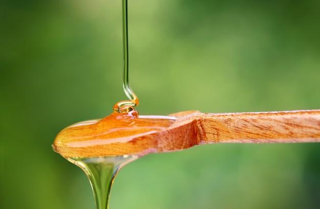 Крупным планом капает мед на деревянной ложкой