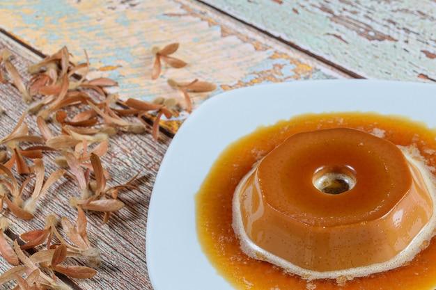 Крупный план пудинга dulce de leche с карамельным сиропом и летающих семян (triplaris americana). традиционная бразильская сладость.
