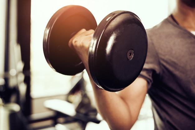 ダンベルのクローズアップ。若い男は重い体重を持ち上げる