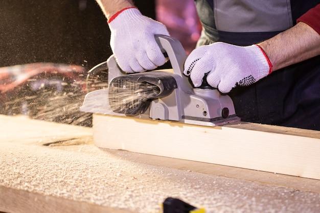 Крупный план электрического самолета, плюющего опилками, пока плотник делает деревянную деталь на верстаке в мастерской коттеджа плотницкие работы по дереву, деревянной стружке. работа в загородном доме
