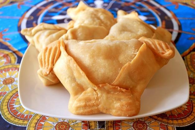 Empanadas의 근접 촬영, 하얀 접시에 제공되는 맛있는 짭짤한 박제 패스트리