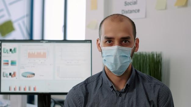 新しい通常の会社のオフィスでchiarに立っている間カメラを見て保護医療フェイスマスクを身に着けている従業員のクローズアップ。 covid19感染を回避するために社会的距離を尊重する労働者