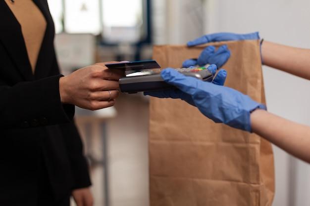 창업 사무실에서 일하는 pos 비접촉식 터미널을 사용하여 신용 카드로 테이크아웃 음식 주문을 지불하는 기업가 여성의 클로즈업. 직장에서 도시락을 가져오는 배달원