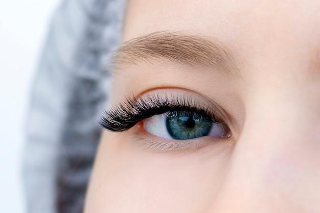 Крупный план глаз с нарощенными ресницами и без нарощенных ресниц