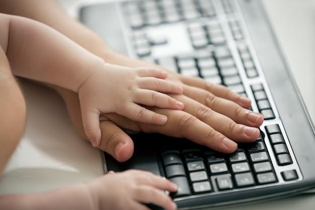 컴퓨터 키보드에 있는 아버지와 아기의 손 클로즈업