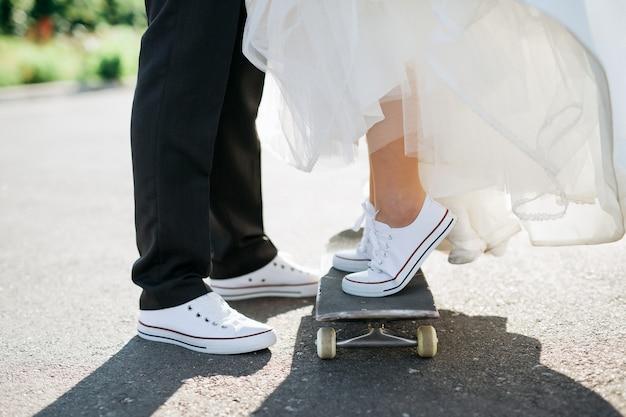 スケートボードで新郎新婦の足のクローズアップ Premium写真