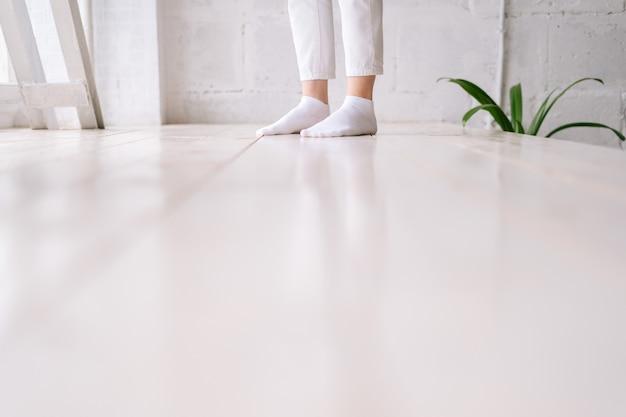 白い床の大きな窓の近くに立っている白い靴下で女性の足のクローズアップ