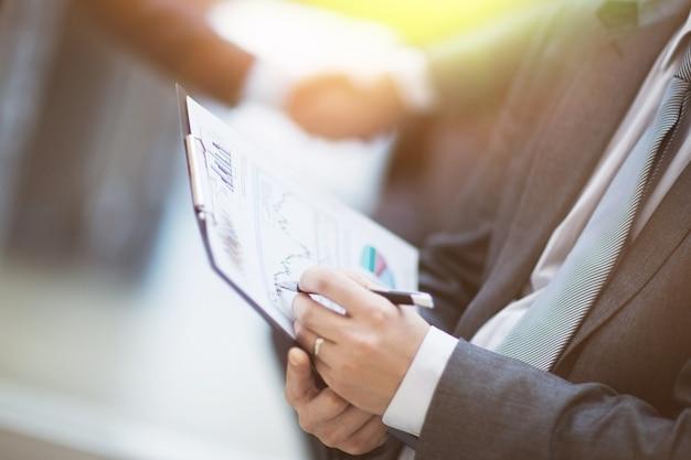 Крупным планом женские и мужские руки, указывающие на деловой документ, работая с ним