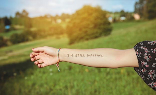 피부에 쓰여진 -나는 아직 기다리고 있다-라는 텍스트가 있는 여성 팔의 클로즈업