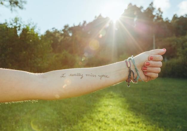 Крупным планом женская рука с надписью «я очень скучаю по тебе», написанной на коже над солнечной природой