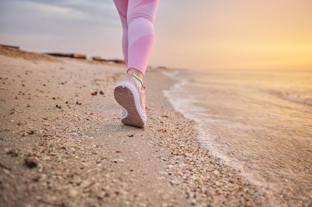 Крупным планом ноги бегуна женщины-спортсменки вдоль побережья моря на фоне песчаного пляжа