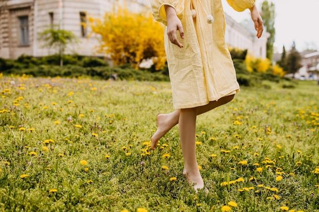 緑の草と花のフィールドで女性の裸足の足のクローズアップ