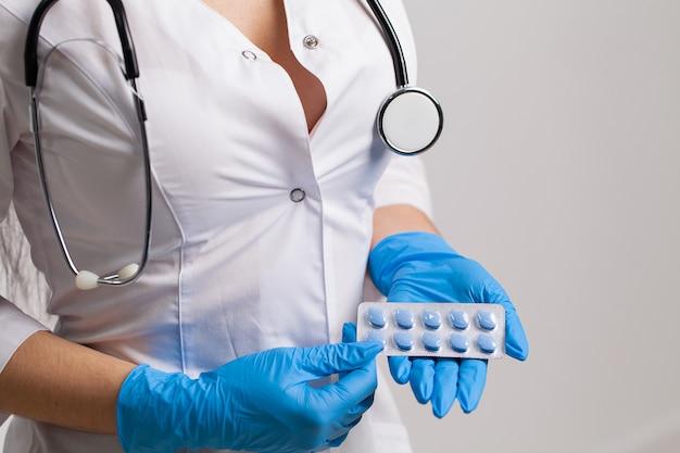 Крупным планом женщина-врач держит таблетку для здоровья мужчин.