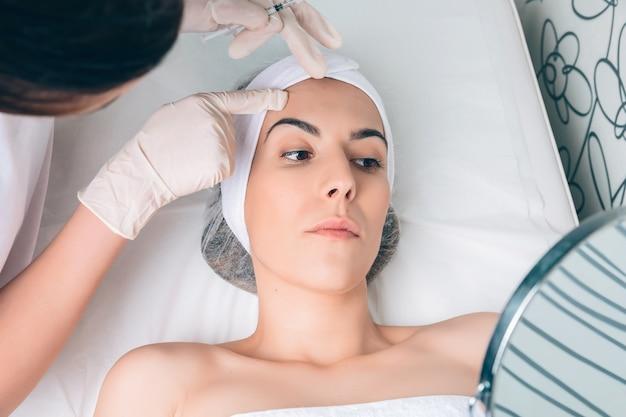 젊은 예쁜 여성에게 클리닉 치료를 적용하기 위해 얼굴 영역을 보여주는 여성 의사의 클로즈업. 의학, 건강 관리 및 미용 개념입니다.