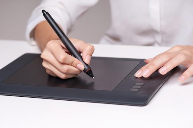 Крупный план женского dressmaker делая эскиз к и рисуя с графической таблеткой. горизонтальная форма, вид сбоку