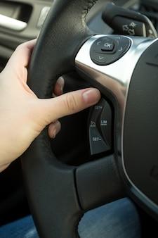 ステアリングホイールのクルーズコントロールシステムを調整する女性ドライバーのクローズアップ