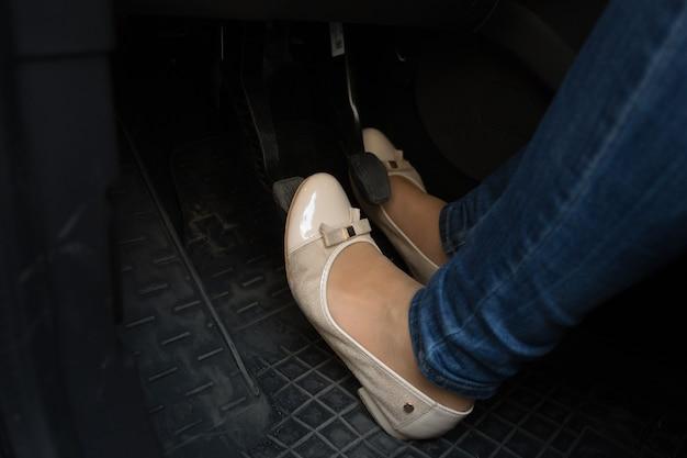 車のペダルの女性ドライバーの足のクローズアップ