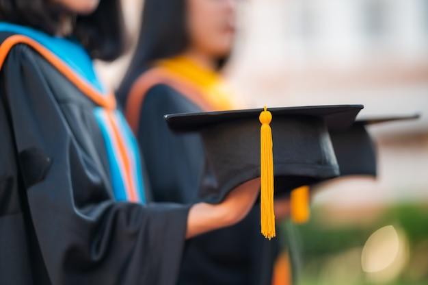 黒い帽子を保持している女性の卒業生、大卒者のクローズアップ