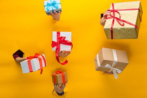 分離された破れた紙を通してプレゼントを持っている女性の手のクローズアップ