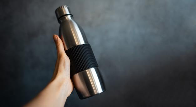 コピー スペースを持つ暗い灰色のテクスチャ壁の背景に鋼のサーモ ウォーター ボトルを持っている女性の手のクローズ アップ。