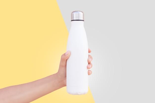 黄色と灰色の 2 つの背景に分離された白い再利用可能な鋼のサーモ ウォーター ボトルを持っている女性の手のクローズ アップ。 2021年の究極のグレーとイルミネーションの色。