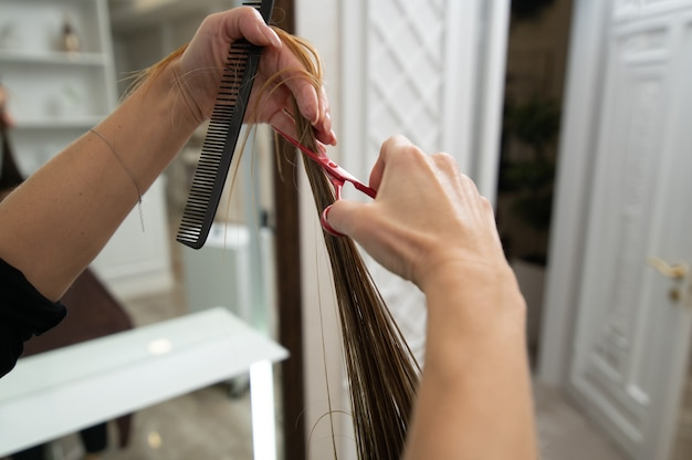 ヘアブラシとはさみを保持し、長い髪を切る女性の手のクローズアップ