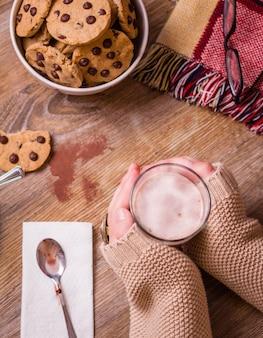 星のボウルにチョコレートチップクッキーとテーブルの上にホットドリンクグラスを保持している女性の手のクローズアップ