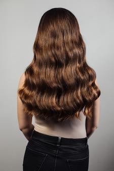Крупный план женских рук парикмахера или coiffeur делает прическу. волосы