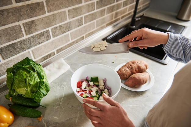 샐러드 그릇에 두부, 채식주의 치즈를 넣어 여성 손의 근접 촬영.