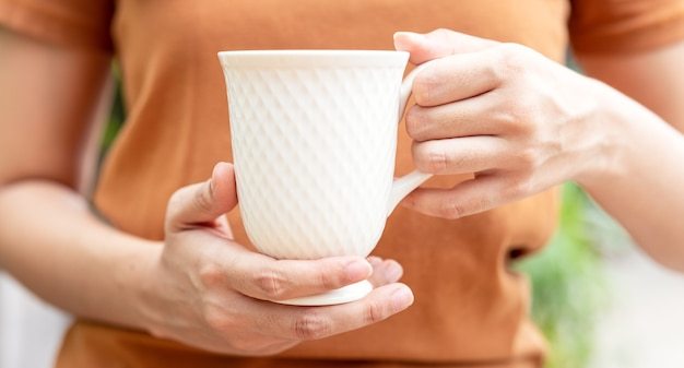 飲み物のマグカップで女性の手のクローズアップ。朝日差しの中でお茶やコーヒーを保持している灰色のセーターの美しい少女。あなたのデザインのためのマグカップ。空の。