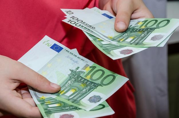 お金で女性の手のクローズアップユーロを与えるか、取るの概念