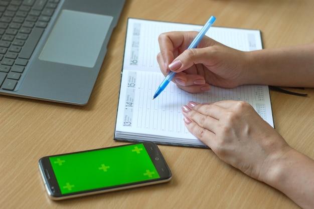 女性の手のクローズアップは、木製のテーブルにノートに書き込み、スマートフォンとラップトップはその隣にあります