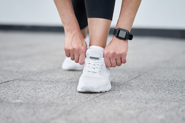 スタイリッシュな白いスニーカーで黒のスポーツレギンスで女性の足のクローズアップ。トレーニングでアクティブなスリムな女性。開始する準備ができました。