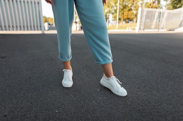 アスファルトのスタイリッシュな革のスニーカーで青いヴィンテージパンツの女性の足のクローズアップ。散歩のファッショナブルな女性。スタイリッシュなスニーカーのモダンな季節のコレクション。女性のファッション。